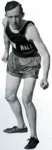 Black and white image of alumnus Melvin Dalton in his Seton Hall track uniform, in a stance so he appears ready to run