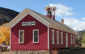 Image of red and white mid-19th century schoolhouse with belfry