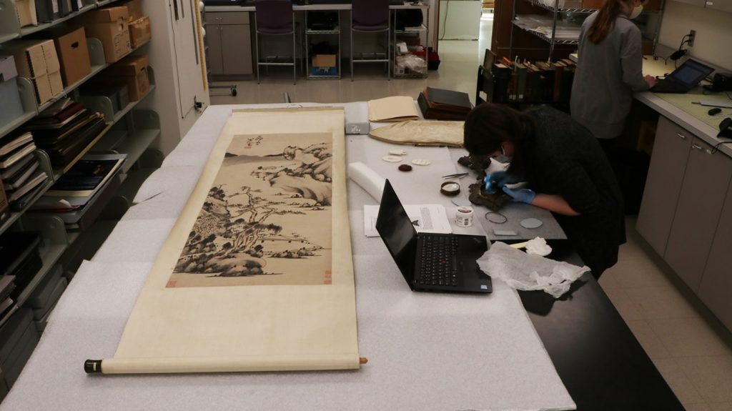 Image of scroll on table with woman inspecting it