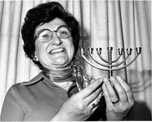 Image of Sister Rose Thering holding a metal menorah