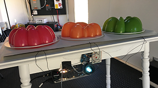 Layered Chiffon project - three 3D printed jello molds on a table with Arduino connected to run simulation when jello molds are pressed.