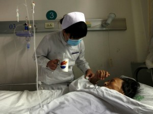 A nurse gives an infected patient medicine as she lies in her bed at the HIV/AIDS ward of Beijing YouAn Hospital on December 1, 2011. (David Gray/Reuters)