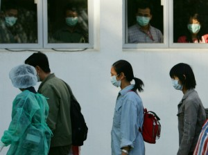 "Observers look out of windows as ""patients"" walk past during a SARS outbreak drill in Hong Kong November 19, 2004. (Bobby Yip/Courtesy Reuters)"
