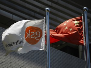 A flag (L) bearing the logo of GlaxoSmithKline (GSK) flutters next to a Chinese national flag outside a GlaxoSmithKline office building in Shanghai on July 12, 2013. (Aly Song/Courtesy Reuters)
