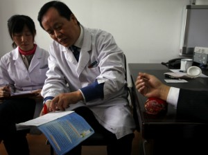 A diabetes patient rests his arm on a table for diabetes specialist Doctor Tong Xiao Lin (C) during a medical check-up at the Guanganmen Chinese medicine Hospital in Beijing March 19, 2012. (David Gray/Courtesy Reuters)
