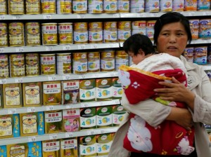 A woman holding a baby stands in front of a shelf displaying milk powder products at a supermarket in Beijing May 20, 2013. (Kim Kyung Hoon/Courtesy Reuters)