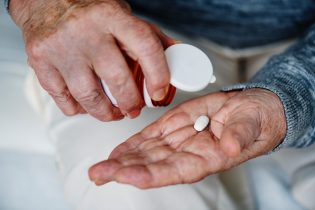 Aged hand with pill