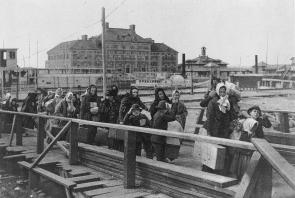 After getting off ships immigrants had to go through processing at Ellis Island before being allowed to come into America. We can see that  the people in the images had to fit all of their possessions from their home countries into two or three suitcases for a new life in another country. We can also see some buildings on Ellis Island in the background.