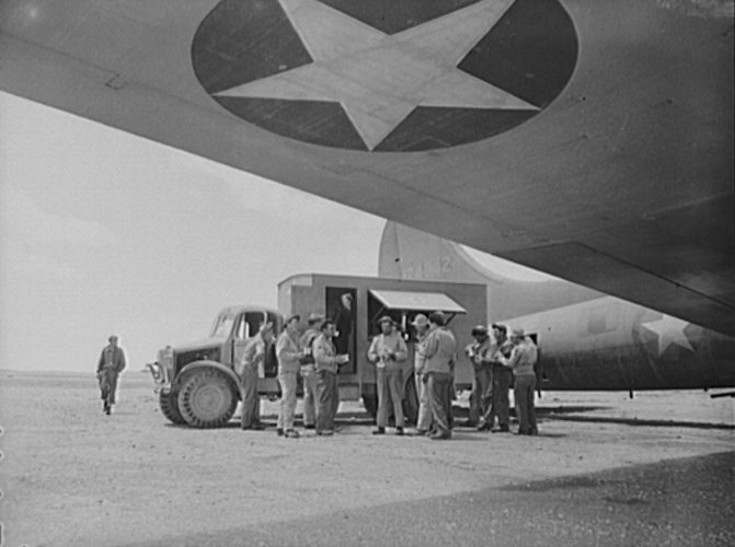 A Red Cross Clubmobile serving doughnuts and coffee to a crew who just returned to the airport from a dangerous mission. From Wikimedia Commons.