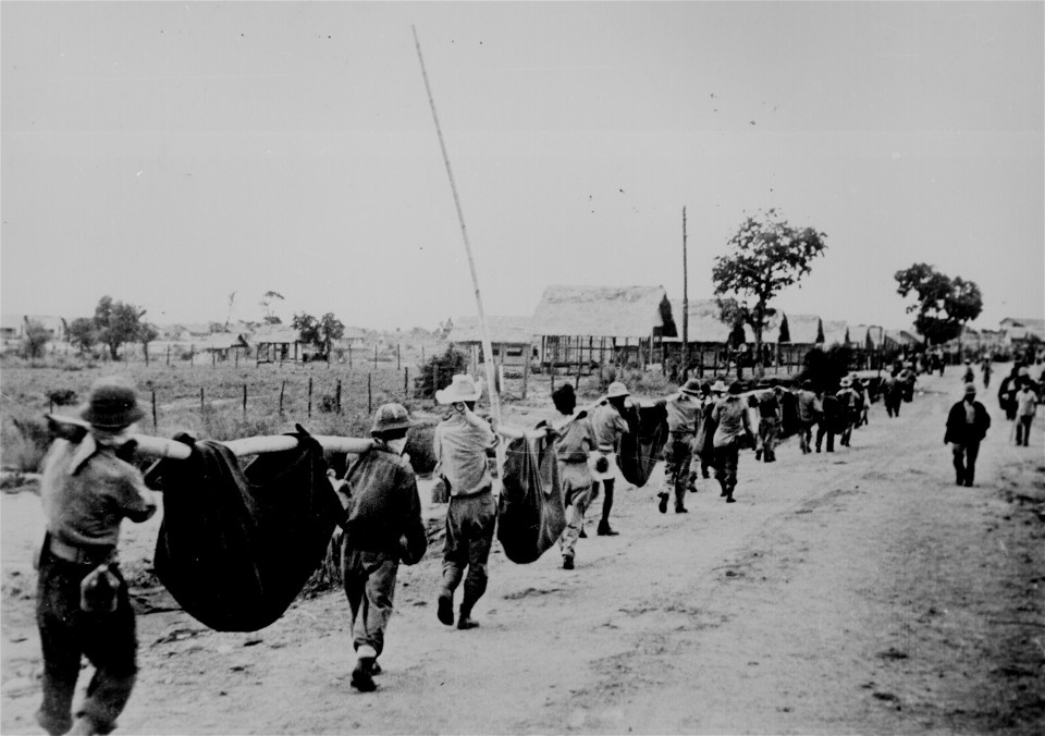 American prisoners using improvised litters to carry their comrades who from the lack of food or water on the march from Bataan, fell along the road. From Wikimedia Commons.
