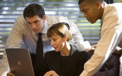 A photo of three businesspeople working together in front of a laptop computer.